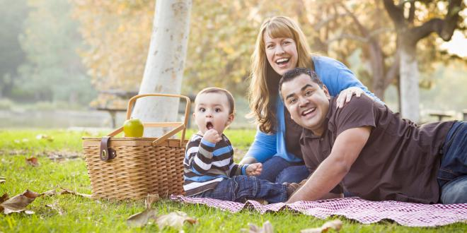 a young family enjoying lunch in the park