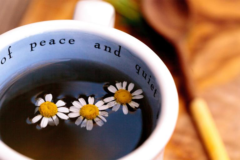 """A cup of chamomile tea. The mug says """"peace and quiet."""""""
